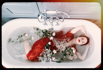 photo of beautiful young woman lying in bath full of flowers and foam and relaxing with her eyes closed. Image with film old frame.