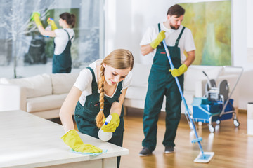 Cleaning service employees with professional equipment cleaning a private home after renovation