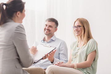 Psychotherapist analyzing a young, happy married couple in a bright office