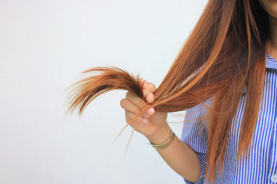 Woman holding at damaged splitting ends of hair, Haircare concept