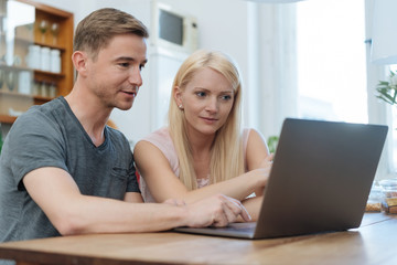 Couple browsing the internet together on a laptop
