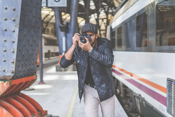Attractive man tourist photographer making photo on analog vintage hipster film camera on train station.Concept travel ideas and freedom lifestyle