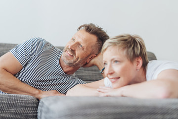 Mature man with woman relaxing on sofa at home