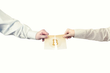 Two hands tear the paper banknote of bitcoin into two parts. Symbol BTC. Bitcoin bifurcation
