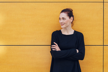 Happy woman with folded arms against yellow wall