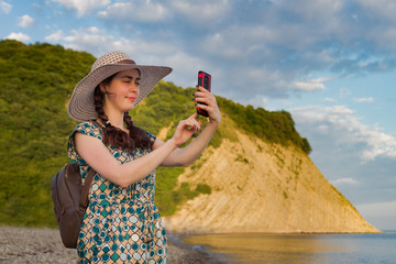 a young girl with a backpack and a hat, traveling taking pictures on a mobile phone landscape, on the background of the mountains and the sea