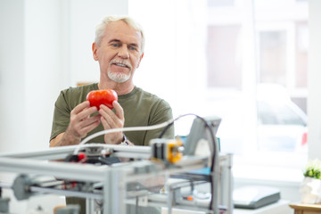 Like the result. Cheerful senior man looking at the printed red tomato printed with 3D printer while being satisfied with the result