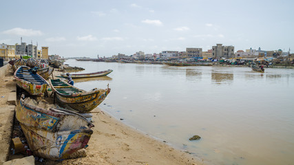 St Louis, Senegal - October 12, 2014: Colorful painted wooden fishing boats or pirogues at coast of St. Louis