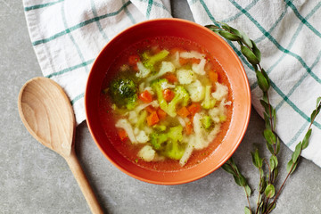 Fresh vegetarian vegetable soup on a grey background, top view. Healthy food, diet