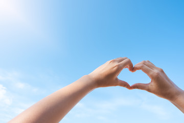 Female hands in heart shape over blue sky background in sunny day.