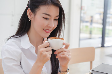 Beautiful attractive young asian business woman smell and drinking coffee in cafe.