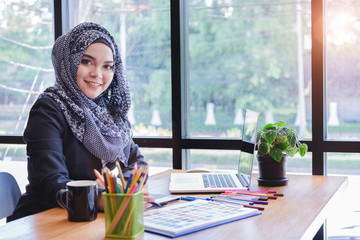 Beautiful young muslim creative designer woman using pen tablets and laptop in front of glass wall office.