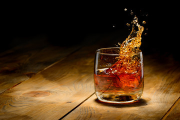 Wall Mural - Whiskey splash in glass on a wooden table.