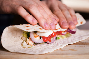 Cooking fresh homemade chicken wrap tortilla on a wooden board