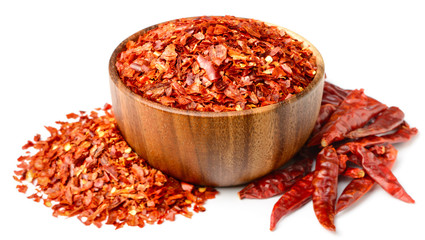 dried red chilli flakes in the wooden bowl, isolated on white