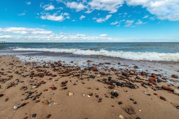 Fototapeta mokre, kolorowe kamyki na piaszczystej plaży obraz