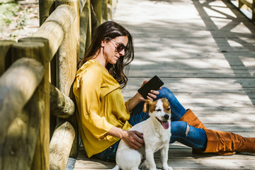 Young beautiful woman taking photograph of her sweet dog playfuly in a lovely park of the center of Madrid. Seated in a wooden floor. Lifestyle