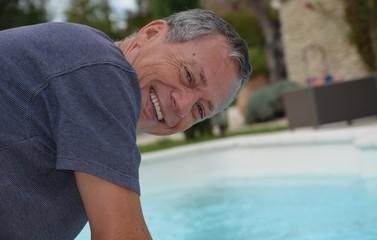 Homme cheveux poivre et sel souriant près de sa piscine.
