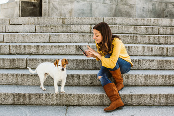 Young beautiful woman taking photograph of her sweet dog playfuly in a lovely park of the center of Madrid. Seated in stone stairs. Lifestyle