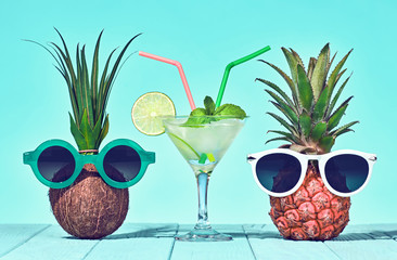Two Hipster Fruits in Trendy Sunglasses, Cocktail on Beach. Tropical Pineapple and Coconut. Bright Color.Fashion Style. Creative Art. Fun Summer party Mood