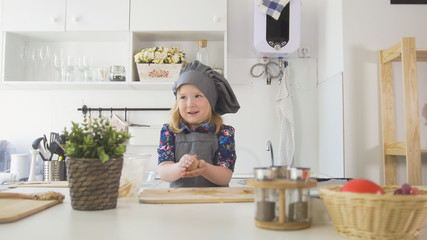 Little caucasian girl in apron rolls out the dough on the board