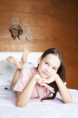 Cute preteen girl in pink t-shirt dreaming on white  bed in boho style room against wooden wall and dreamcatchers. Scandinavian interior, Swiss chalet. Youth, lifestyle concept. Text space