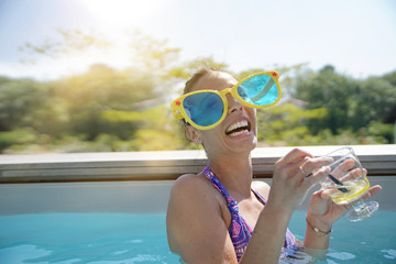 Girl in swimming-pool with cocktail and huge funny sunglasses
