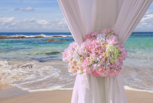 Curtain tied with flowers on beach