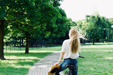 attractive beutiful blonde woman girl with bicycle or bike relaxing or having fun in a park, summer holiday, trip, leisure time, sport