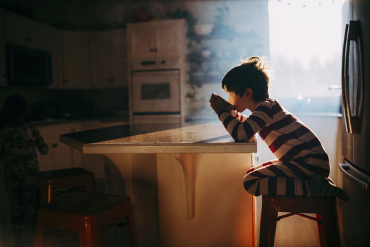 Boy sitting in kitchen eating his breakfast in morning light