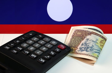 Five hundreds of banknote currency Lao Kip with calculator on the white floor with Laos nation flag background. It is the money of Laos in 1988, and the concept of finance.