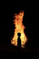 Silhouette of a young boy in front of a fire