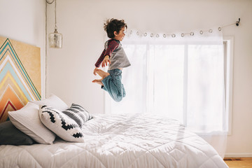Boy jumping on a bed