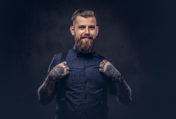 Smiling handsome old-fashioned hipster in a blue shirt and suspenders, posing in a studio.