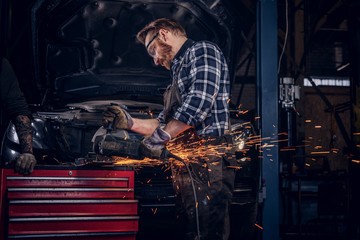 Two bearded auto mechanic in a uniform and safety glasses working with an angle grinder while standing against a broken car in repair garage.