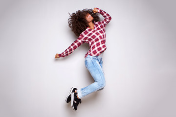 Full body excited young woman jumping in air against white background