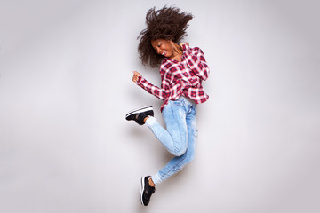 Full body cheerful young african woman jumping in air over white background