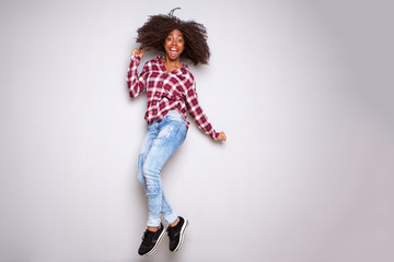 Full body excited young black woman jumping with joy over white background