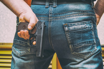 Man in jeans holding a gun behind his back