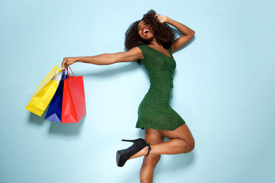 excited young woman with shopping bags on blue background