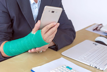 business woman with green cast on arm holding smart phone and working on laptop in office, focus on broken hand