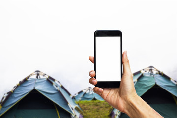 Hand holding black smartphone with white screen for mock up on camping tent as background.