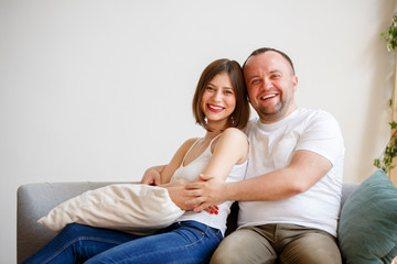 Image of smiling married couple sitting on sofa