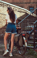 Sexy slim girl wearing short denim shorts and a white t-shirt walking with the city bicycle near an old abandoned brick building.