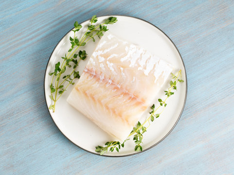 piece of raw cod fish fillet on plate on blue wooden table, top view