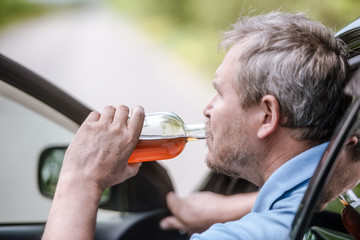 Man driving a car with a bottle of alcohol drink. Don't drink and drive concept