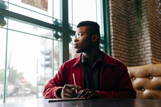 Black man sitting in cafe and writing looking through the window