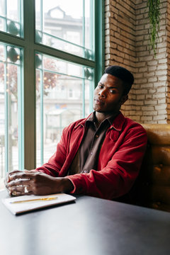 Black man sitting in cafe looking away thoughtful