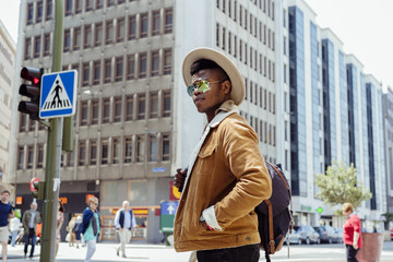 Young african male in hat and glasses walking on the street