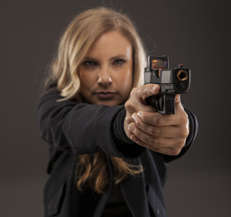 Blonde woman aiming a gun.